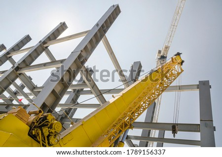 Metal columns and girders in construction site Low angle perspective of steel girders and tall crane #1789156337
