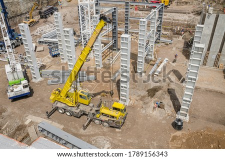 Metal columns and girders in construction site High view of foundation with steel girders and tall crane #1789156343