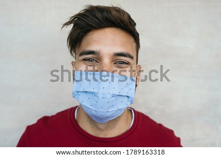 Young man wearing face mask portrait - Latin boy using protective facemask for preventing spread of corona virus - Health care and youth millennial people concept  #1789163318