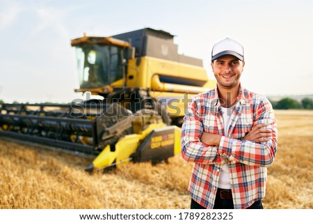 Portrait of proud harvester machine driver with hands crossed on chest. Farmer standing at his combine. Agronomist looking at camera. Rancher at harvesting work on stubble of harvested wheat field. #1789282325