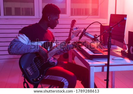 Musician and making music concept - African american male sound producer working in recording studio. Royalty-Free Stock Photo #1789288613