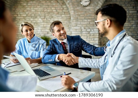 Happy financial advisor and male doctor shaking hands after successful meeting in the office. Royalty-Free Stock Photo #1789306190