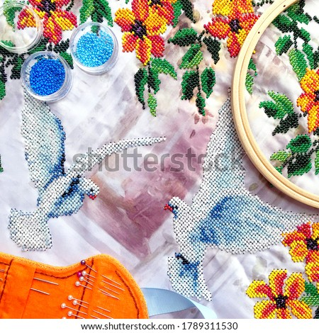 Beads embroidery of dove birds & orange flowers with leaves. Embroidery beads work on table - beads, hoop, needles. Close-up woman embroidery beads work top view two pigeon and flowers pattern #1789311530
