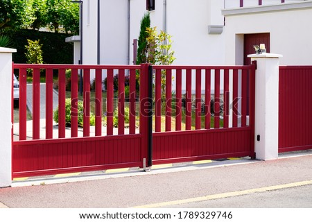 Aluminum dark red metal gate of suburb house steel door Royalty-Free Stock Photo #1789329746