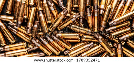 Empty cartridge cases for a carbine or rifle. Background of shiny brass cartridges for cartridges to illustrate armed conflict, war or shooting events. Military back. #1789352471
