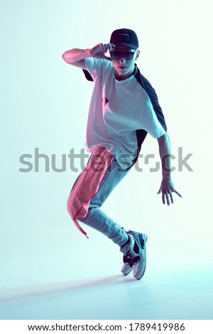 Cool young guy dance contemporary dance in studio in neon light. Break dance lessons. Dance school poster #1789419986