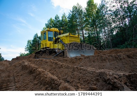 Dozer during clearing forest for construction new road . Yellow Bulldozer at forestry work Earth-moving equipment at road work, land clearing, grading, pool excavation, utility trenching #1789444391