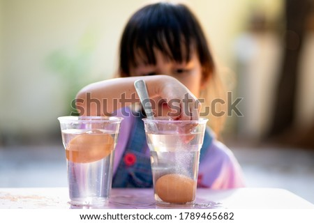 Easy science experiment at home to learn about the density of salt water effect to floating and sinking of the eggs, concept of child education and learning through play activity at home Royalty-Free Stock Photo #1789465682