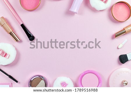 Flat lay with various makeup beauty products like brushes, powder or lipstick surrounding pastel pink background with empty copy space