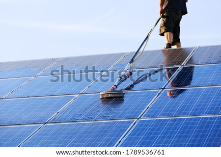 Cleaning solar panels with brush and water Royalty-Free Stock Photo #1789536761