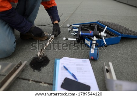 Safety workplace trained safety auditor wearing black safety glove inspecting using spanner tensioning industrial working at heights fall arrest, stainless 16 MM dimension certifies anchor lifeline