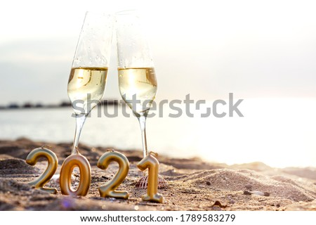 Two glasses of champagne and figures with numbers of the new year 2021 on the sand on the beach against the background of the sea. Space for text. Spend Holidays and celebration on the beach concept #1789583279