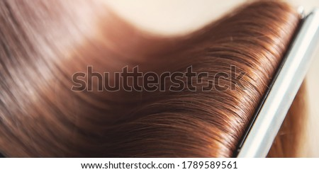 Close up hands of professional hairdresser beauty salon, straighteners curling female hair. Royalty-Free Stock Photo #1789589561
