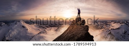 Magical Fantasy Adventure Composite of Man Hiking on top of a rocky mountain peak. Background Landscape from British Columbia, Canada. Sunset or Sunrise Colorful Sky #1789594913