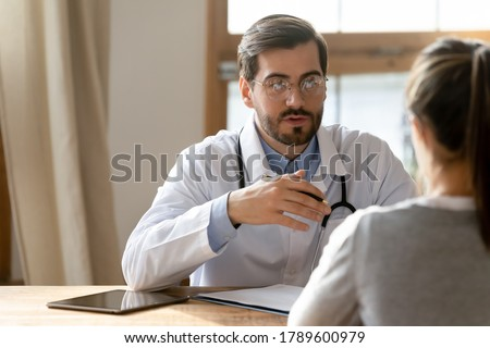 Head shot focused male general practitioner doctor in eyeglasses and white uniform giving professional consultation to young female patient at checkup clinic meeting, healthcare medical insurance. Royalty-Free Stock Photo #1789600979