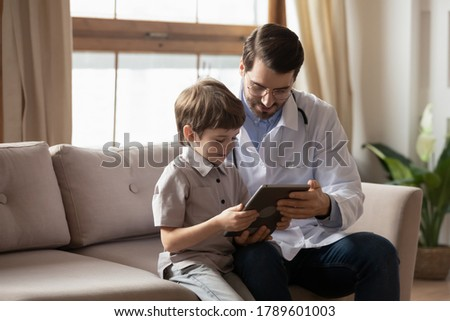 Friendly young male pediatrician in medical coat showing cartoons games on tablet to little kid patient, special approach to children. Doctor helping small boy getting relaxed at checkup meeting.