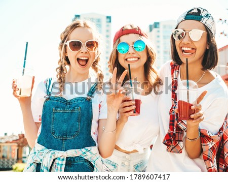Three young beautiful smiling hipster girls in trendy summer clothes.Sexy carefree women posing outdoors.Positive models holding and drinking fresh cocktail smoothie drink in plastic cup with straw #1789607417