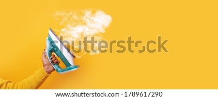modern iron with steam in hand over yellow background, panoramic mock-up image Royalty-Free Stock Photo #1789617290