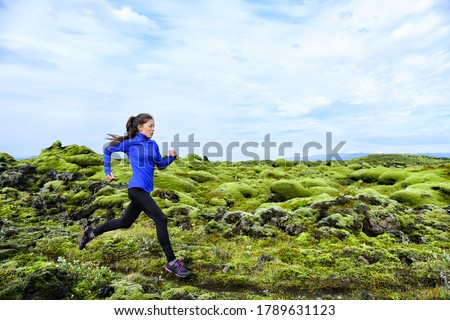 Woman running. Trail runner in cross country run. Female runner training jogging outdoors in mountain nature landscape on Iceland. Healthy lifestyle mixed race fitness model.
