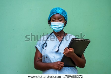 Portrait of an African health care provider holding patient documents and stethoscope around neck,wearing face mask and head gear for protection Royalty-Free Stock Photo #1789688372