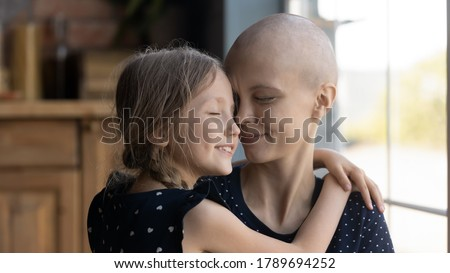 Happy young Caucasian cancer patient sick mother and little daughter hug show love and care, supportive small girl child embrace caress ill hairless mom suffer from oncology, feel grateful thankful Royalty-Free Stock Photo #1789694252