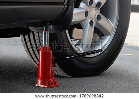 The red hydraulic bottle jack is installed under the machine and lifting it. Royalty-Free Stock Photo #1789698842