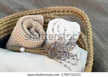 Trendy decor for cozy home. Beautiful items from natural materials. Rolled towel, folded beige cloth, lavender bouquet in a basket. Close up. Nobody. Horizontal. Concept smells, spa, bath decor. Royalty-Free Stock Photo #1789732313