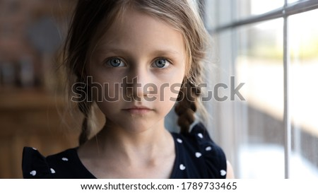 Crop close up portrait of serious sad little Caucasian girl look at camera, unhappy small child kid orphan feel lonely abandoned, outcast or loner miss parents, children drama, volunteer concept #1789733465