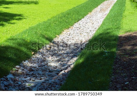 drainage, a drainage system in a Park area, a waterway overgrown with lawn and paved with stones, an Aqueduct between nature and the road. stone water drains in a grass garden field. Lawn and plant #1789750349