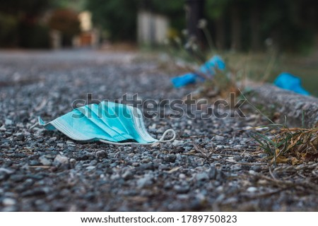 Medical face mask on the floor in the street.Disposable Face Mask.Used Surgical masks haphazardly strewn on pavement.Improperly discarding used face mask. Lost face mask at pavement Royalty-Free Stock Photo #1789750823