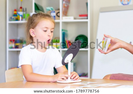 developmental and speech therapy classes with girl. Speech therapy exercises and games with a mirror and cards Royalty-Free Stock Photo #1789778756