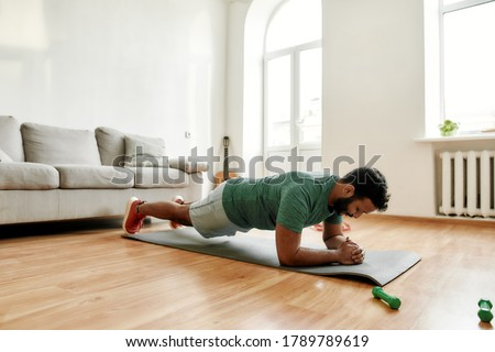Perseverance matters. Young active man looking focused, exercising, doing plank during morning workout at home. Sport, healthy lifestyle. Horizontal shot Royalty-Free Stock Photo #1789789619