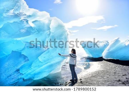 Iceland Amazing landscape at Iceberg beach. Tourist by icebergs on Ice beach, Breidamerkursandur aka Diamond Beach by jokulsarlon glacial lagoon / glacier lake nature. Woman in icelandic sweater. Royalty-Free Stock Photo #1789800152