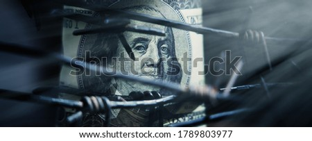 Economic confrontation and warfare, sanctions and embargo busting concept. Barbed wire against US Dollar bill. Horizontal image.