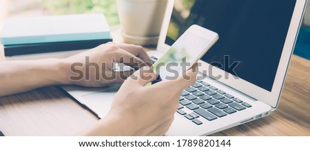 Hand of business man working from home using laptop computer to internet online on desk, new normal, social distancing, freelance work and look phone, communication concept, banner website. Royalty-Free Stock Photo #1789820144