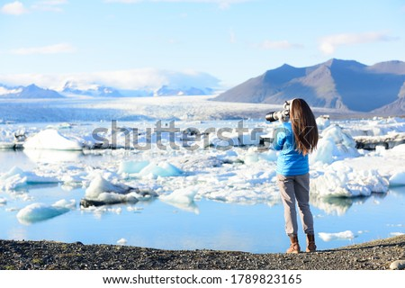 Photographer tourist woman taking photos with DSLR camera on travel on Iceland by Jokulsarlon glacial lagoon / glacier lake on Iceland. Happy tourist women on travel in beautiful nature landscape.