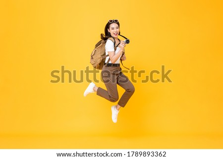 Young pretty Asian woman tourist backpacker smiling and jumping with camera in hand isolated on yellow background #1789893362