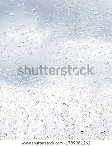 Rain drops on window glasses surface with cloudy sky background . Natural backdrop of raindrops. Abstract overlay for design. The concept of bad rainy weather.