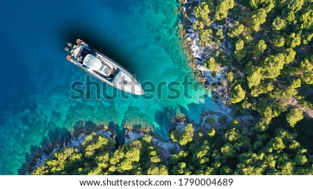 Aerial drone top down photo of inflatable speed boat anchored in tropical exotic island covered with pine trees Royalty-Free Stock Photo #1790004689