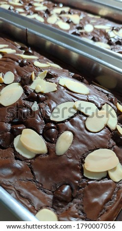 Brownies with shiny crust and almond slice on top, selective focus, contain sharpening noise, grainy texture, blurry background, unfocused picture