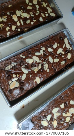 Chocolate fudge brownies with shiny crust, unfocused picture, blurry background, noise and grain texture, reflected by light