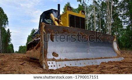 Dozer during clearing forest for construction new road . Yellow Bulldozer at forestry work Earth-moving equipment at road work, land clearing, grading, pool excavation, utility trenching #1790017151