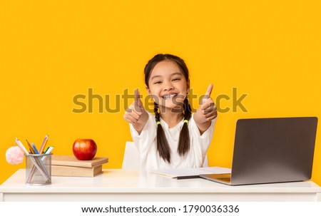 Smiling Asian Elementary School Girl At Laptop Gesturing Thumbs Up Sitting At Desk On Yellow Studio Background. I Like E-Learning. Royalty-Free Stock Photo #1790036336