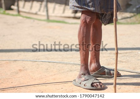 Old aged man with a pair of ripped sandals and standing on road with walking stick.Legs visible.Closeup/detail shot. Pensionar/jobless/alone/sad hopeless person wearing a lungi.Copyspace.Wrinkled skin