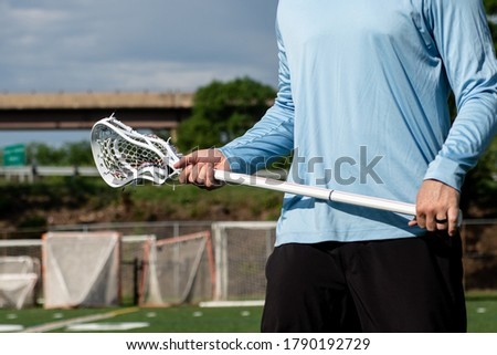 Male lacrosse player holding a lacrosse stick on a field
