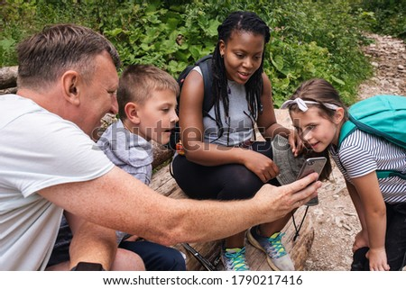 Smiling father showing his two children and a friend pictures on his cellphone during a hike together in a forest