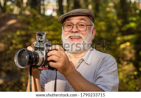 Vintage camera. Hire vacation photographer. portrait of joyful elderly man making photo. nice shot. retro photographic equipment. Say cheese. DSLR camera is being used to photograph wild plants.