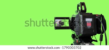 Broadcast camera in studio with green screen at TV station.
