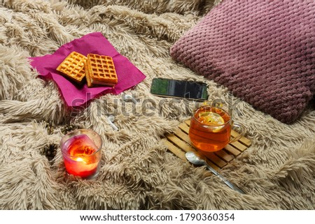 Autumn.Home. warm.  Comfort. Cup of tea, dessert and candles on the background of a cozy blanket. Autumn cozy evening by candlelight with a Cup of tea with lemon.. #1790360354