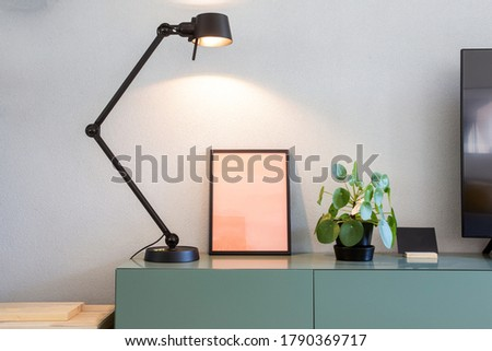 Stylish modern interior, empty picture frame with black lamp and green Chinese Money plant, retro pancake plant on green table scandinavian design close-up
